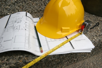 Hard hat on plans with a pencil and a measuring tape